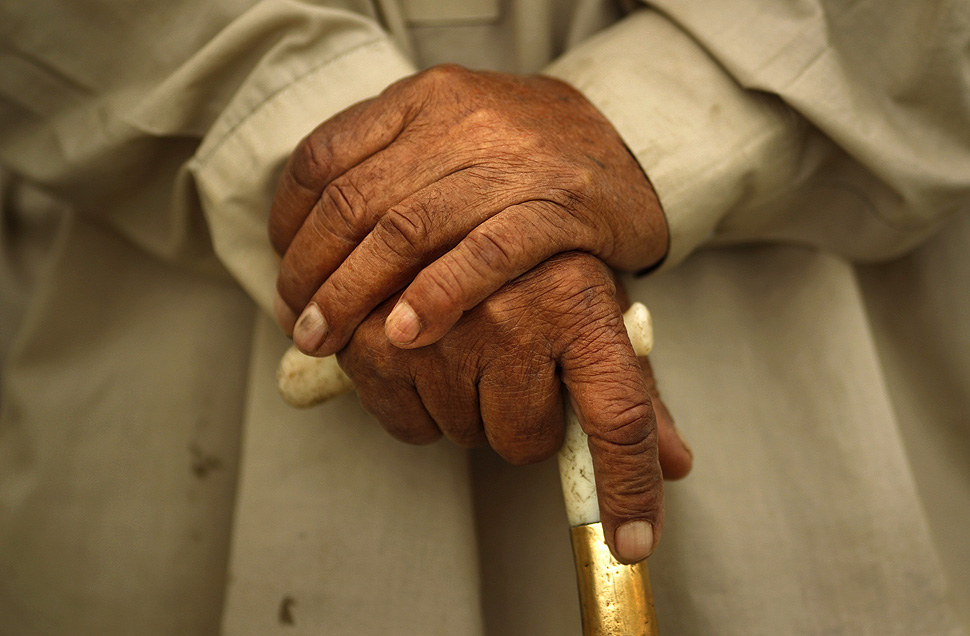 100-year-old local resident Babou Zay holds his walking stick as he talks to a journalist about his damaged house near Mingora in Pakistan's Swat Valley